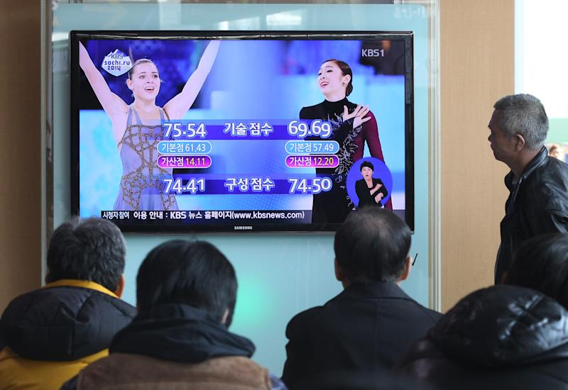"""People watch a TV news report with images of Russia's Adelina Sotnikova, left, and South Korea's Yuna Kim about the result of the women's free skate figure skating final during the 2014 Winter Olympics, at the Seoul Railway Station in Seoul, South Korea, Friday, Feb. 21, 2014. South Koreans still love Yuna Kim. The judges, however, are another matter. Kim, known as the """"Queen"""" in South Korea, finished with the figure skating silver medal at the Sochi Olympics behind Adelina Sotnikova of Russia. That left many South Koreans furious over what they saw as questionable judging. (AP Photo/Ahn Young-joon)"""