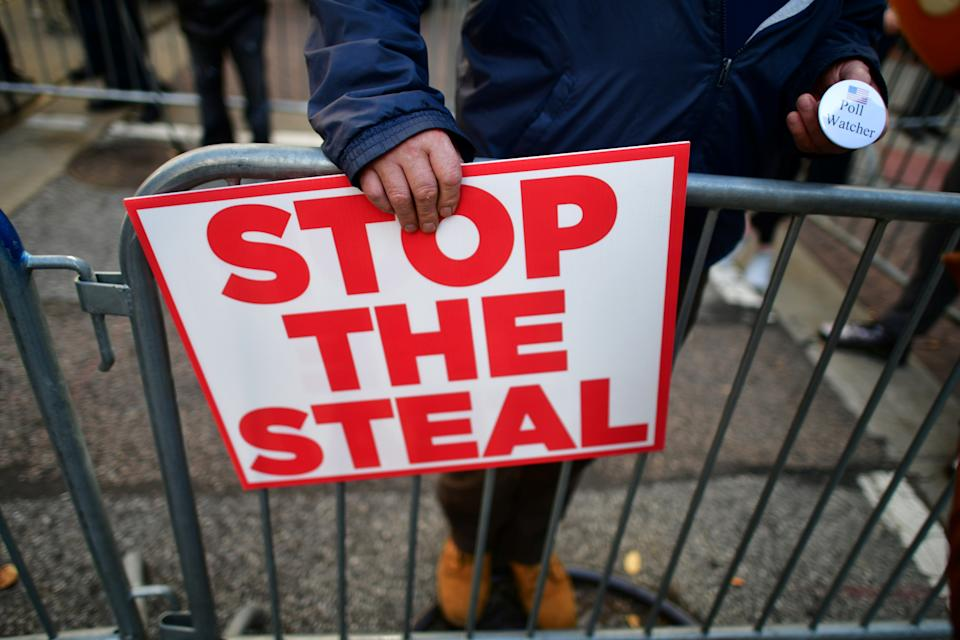 "A supporter of President Donald Trump holds a sign stating ""STOP THE STEAL"" and a pin stating ""Poll Watcher""in Philadelphia, Pennsylvania on November 6, 2020. (Mark Makela/Reuters)"