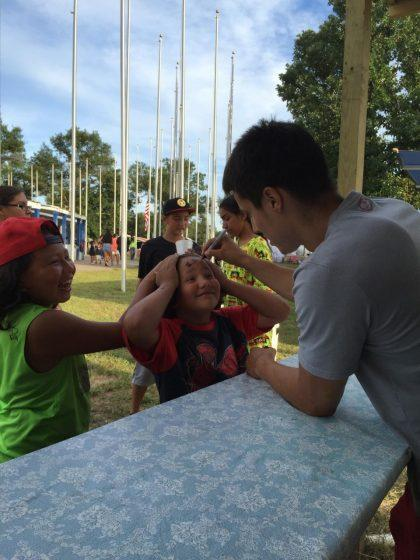 Bronson Koenig signs a young fan's forehead at the Ho-Chunk Powwow earlier this month (via Clint Parks)