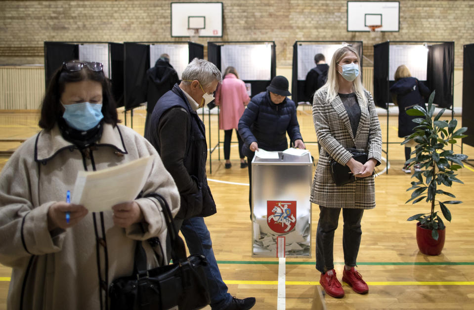 People wear face masks to protect against coronavirus as they cast their ballots during the parliamentary elections in Vilnius, Lithuania, Sunday, Oct. 11, 2020. Polls opened Sunday for the first round of national election in Lithuania, where voters will renew the 141-seat parliament and the ruling four-party coalition is widely expected to face a stiff challenge from the opposition to remain in office. (AP Photo/Mindaugas Kulbis)