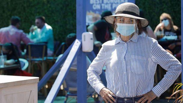 PHOTO: A hostess waits to sit customers at a restaurant on the pier, July 12, 2020, in Santa Monica, Calif., amid the coronavirus pandemic. (Marcio Jose Sanchez/AP)