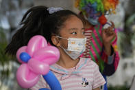 A child wearing a face mask to help curb the spread of the coronavirus reacts with a flower-shaped balloon after receiving from a masked clown during a children event in Beijing, Sunday, May 30, 2021. (AP Photo/Andy Wong)