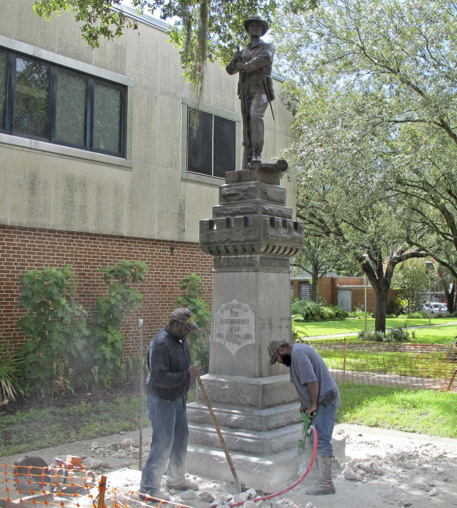 <p>Workers begin removing a Confederate statue in Gainesville, Fla., Monday, Aug. 14, 2017. The statue is being returned to the local chapter of the United Daughters of the Confederacy, which erected the bronze statue in 1904. County officials said they did not know where the statue would be going. (Photo: Jason Dearen/AP) </p>