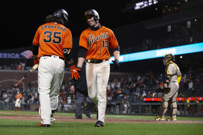 San Francisco Giants' Austin Slater (13) gets a congratulatory handshake from Brandon Crawford (35) after hitting a solo home run against the San Diego Padres during the seventh inning of a baseball game Friday, May 7, 2021, in San Francisco. (AP Photo/D. Ross Cameron)
