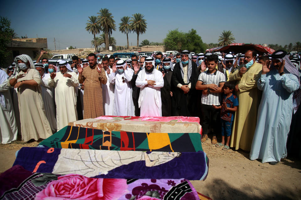 Mourners pray over the coffins of civilians killed by a Katyusha rocket attack near the international airport in Baghdad, Iraq, Tuesday, Sept. 29, 2020. Several Iraqi civilians were killed and two severely wounded Monday after the rocket hit near Baghdad airport, Iraq's military said. It was the first time in months an attack caused civilian casualties.(AP Photo/Khalid Mohammed)
