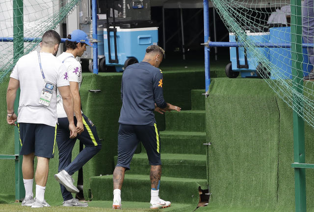 Brazil's Neymar, right, leaves a training session because of pain in his right ankle, in Sochi, Russia, Tuesday, June 19, 2018. Brazil will face Costa Rica on June 22 in the group E for the soccer World Cup. (AP Photo/Andre Penner)