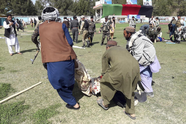 A wounded man is carried away following multiple explosions in Lashkar Gah city of Helmand province, southern Afghanistan, Saturday, Mar. 23, 2019. An Afghan official says that at least three have been killed in twin bomb explosions occurred during the Farmer's Day ceremony in southern Helmand province. (AP Photo/Abdul Khaliq)