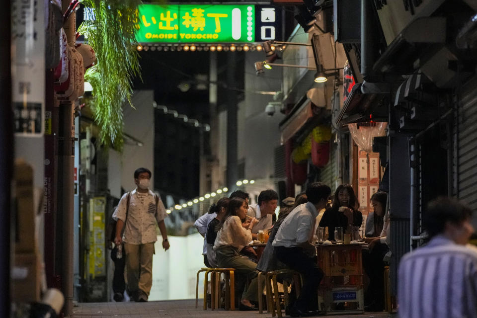 People gather at bars that are open and serving alcohol on an ally filled with bars and restaurants despite Tokyo government has requested businesses not to serve alcohol under the state of emergency Wednesday, Sept. 22, 2021, in Tokyo. Japan is set on Tuesday, Sept. 28, 2021 to lift ongoing coronavirus state of emergency and less-stringent measures in all 27 prefectures including Tokyo when they expire at the end of September as the infections slow and the nation tries to reactivate its economy. (AP Photo/Kiichiro Sato)