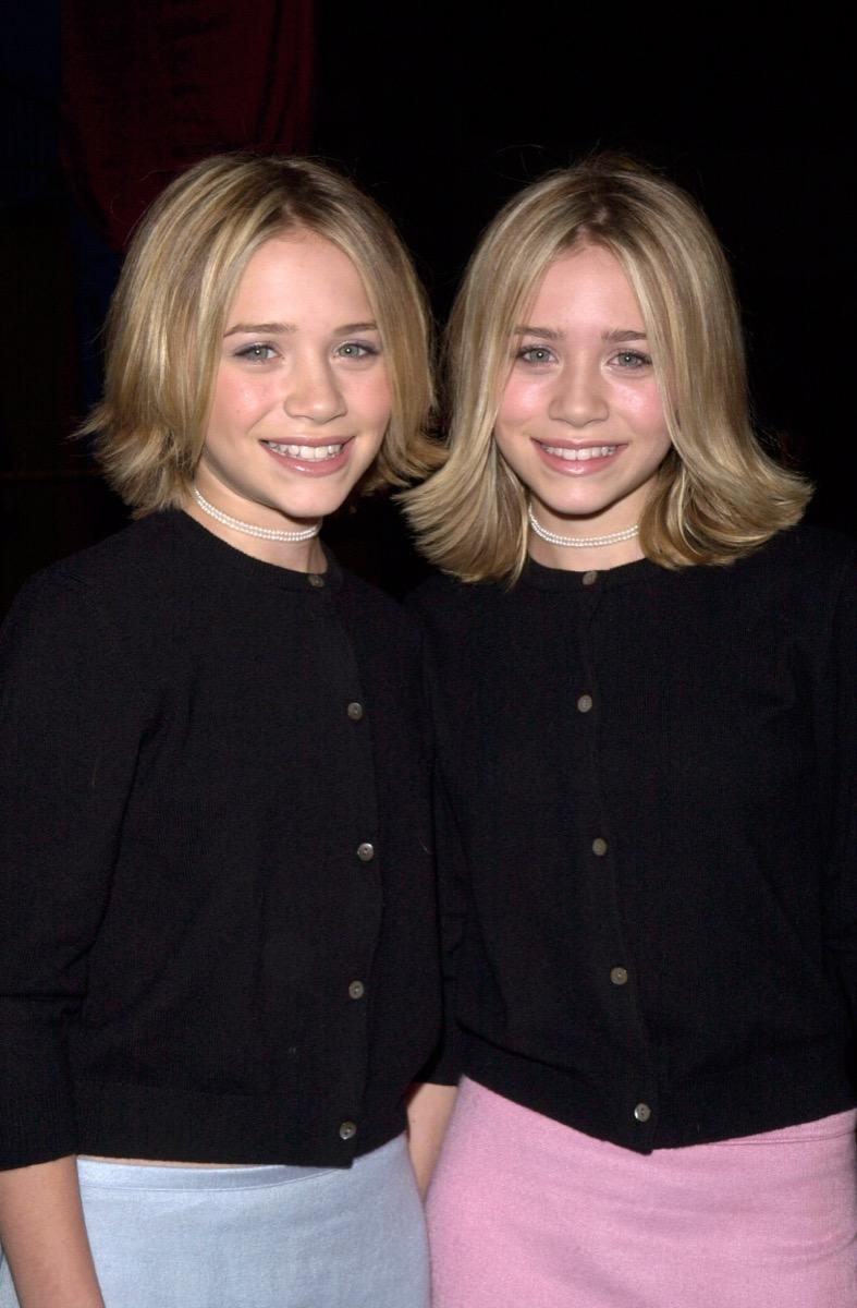 Mary-Kate And Ashley Olsen in black cardigans and blue and pink pencil skirts in 1999