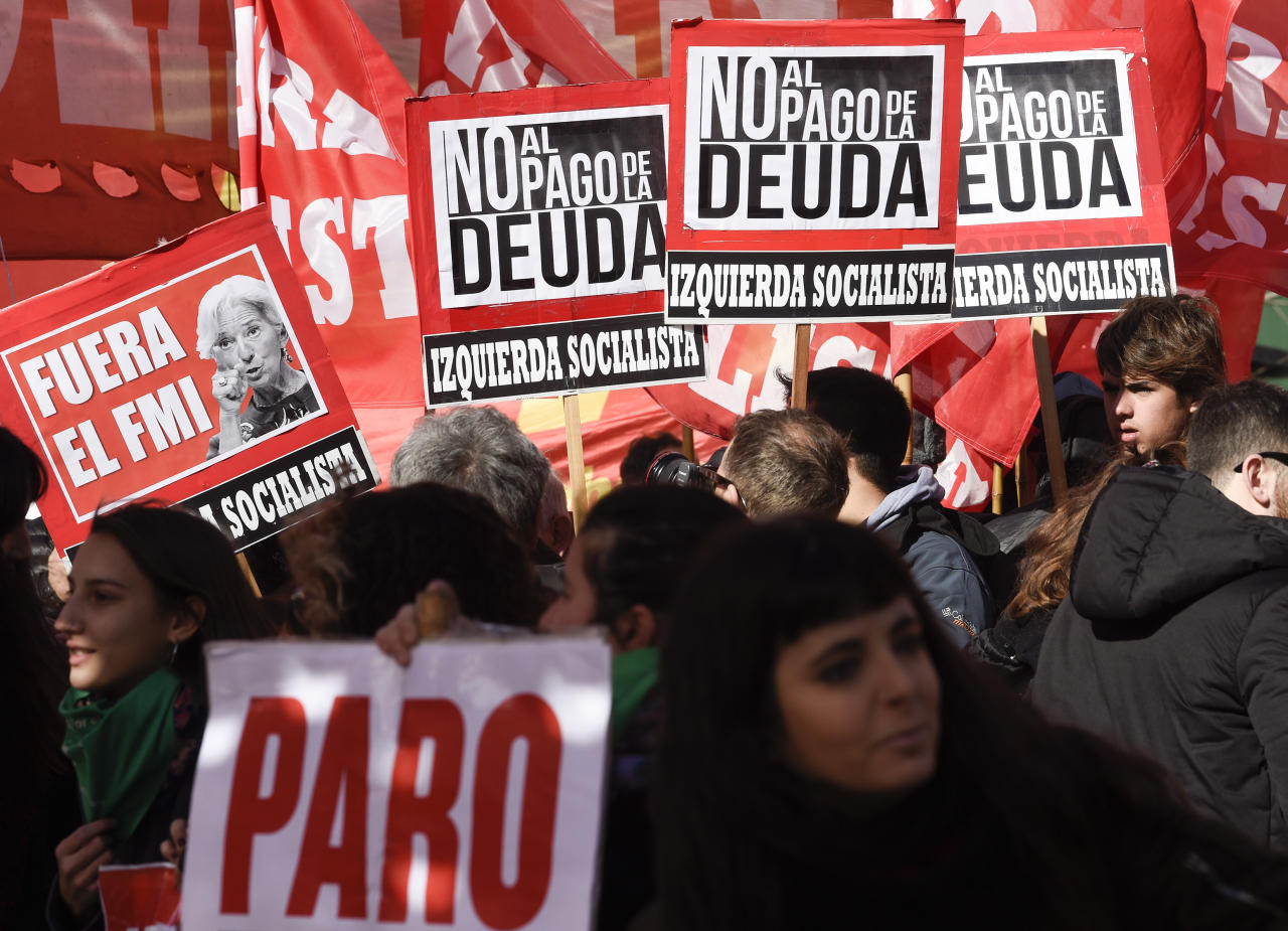 """Political parties opponents and social movements protesters hold signs that read in Spanish: """"Out IMF and No to the payment of the debt, """" one showing an image of with a picture of Christine Lagarde, International Monetary Fund Managing director, during a demonstration against the IMF near the G20 Finance Minister and Central Bank governors meeting in Buenos Aires, Argentina, Saturday, July 21, 2018. (AP Photo/Gustavo Garello)"""