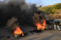 A protester burns tires to block a highway that leads to Beirut's international airport, during a protest against against the economic and financial crisis, in Beirut, Lebanon, Tuesday, March 2, 2021. The Lebanese pound has hit a record low against the dollar on the black market as the country's political crisis deepens and foreign currency reserves dwindle further. (AP Photo/Hussein Malla)