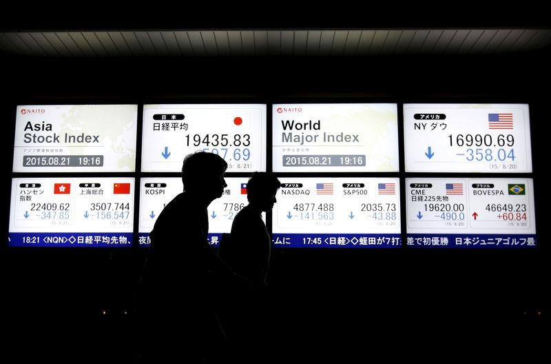FILE PHOTO: People walk past an electronic board displaying various Asian countries' stock price index and world major index outside a brokerage in Tokyo, Japan, August 21, 2015. REUTERS/Issei Kato/File Photo