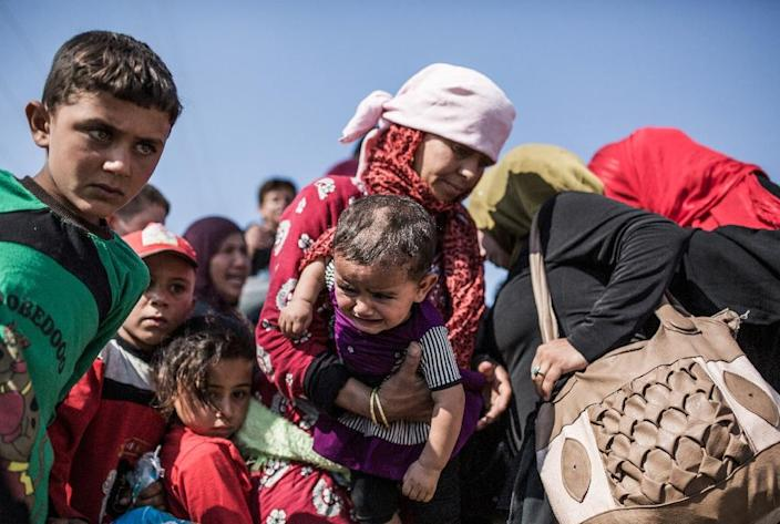Syrian refugees who had fled Tal Abyad re-enter the country from Turkey on June 22, 2015, after Kurdish People's Protection Units took control of the area (AFP Photo/Uygar Onder Simsek)