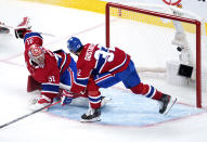 The puck sails into the net past Montreal Canadiens goaltender Carey Price on a goal by Tampa Bay Lightning's Tyler Johnson, as defenseman Erik Gustafsson looks on during the second period of Game 3 of the NHL hockey Stanley Cup Final, Friday, July 2, 2021, in Montreal. (Paul Chiasson/The Canadian Press via AP)