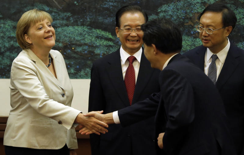 Chinese Premier Wen Jiabao, center, reacts as German Chancellor Angela Merkel, left, shakes hands with an unidentified Chinese official as Chinese Foreign Minister Yang Jiechi at right looks on during a signing ceremony at the Great Hall of the People in Beijing, China, Thursday, Aug. 30, 2012. (AP Photo/Ng Han Guan)