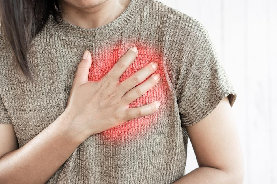 woman hand touching her chest having heart attack