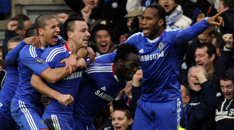 FILE - In this Jan. 2, 2011 file photo, Chelsea's John Terry, center, celebrates with teammates, from left,  Ashley Cole, Jeffrey Bruma, Michael Essien and Didier Drogba after scoring during their English Premier League soccer match against Aston Villa at the Stamford Bridge Stadium in London. On Feb. 1, Terry will appear at a London courthouse to face a criminal charge that he abused a black colleague with a torrent of vile, racially insulting language. Terry insists the whole affair is a misunderstanding. Born and raised in the ethnic melting pot of east London, he has played with or alongside black footballers all of his sporting life.  (AP Photo/Tom Hevezi, File)
