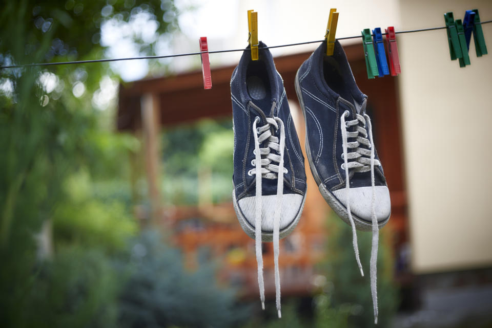 Pair of Black sneakers drying on a rope.