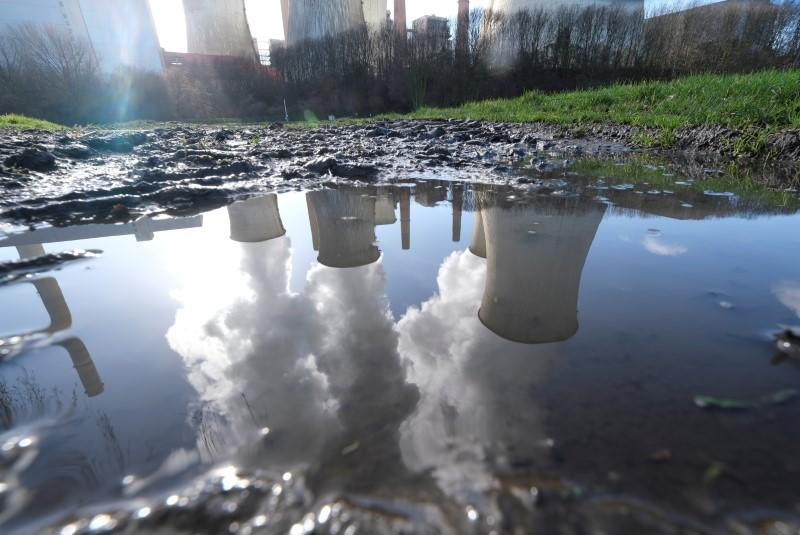 FILE PHOTO: The lignite power plant complex of German energy supplier and utility RWE is reflected in a puddle in Neurath
