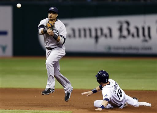 New York Yankees second baseman Robinson Cano, left, forces Tampa Bay Rays' Ben Zobrist (18) at second base and throws to first in time to turn a fifth-inning double play on Rays' Evan Longoria during a baseball game, Monday, April 22, 2013, in St. Petersburg, Fla. (AP Photo/Chris O'Meara)