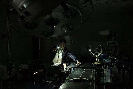 A nurse uses light from a phone while he looks for material in an out-of-use operating room of the Padre Justo hospital, during a blackout in Rubio, Venezuela March 14, 2018. Picture taken March 14, 2018. REUTERS/Carlos Eduardo Ramirez TPX IMAGES OF THE DAY