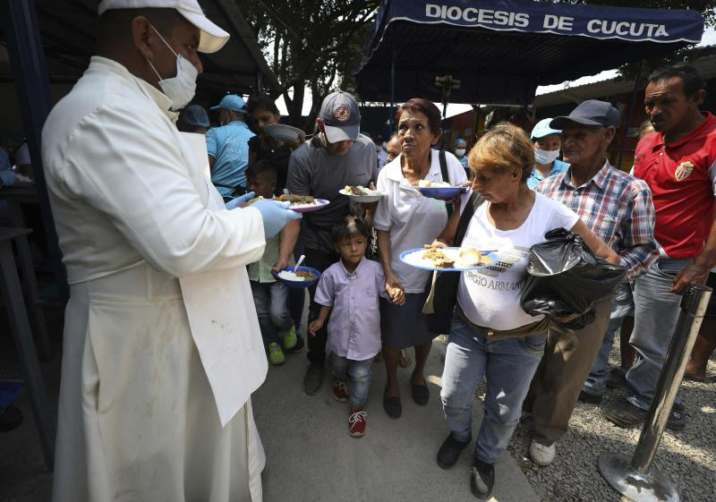 "Priest Richard Garcia hands out free lunches to Venezuelan migrants at the ""Divina Providencia"" migrant shelter in La Parada, near Cucuta, on the border with Venezuela, Colombia, Monday, Feb. 11, 2019. Millions of Venezuelans have migrated, and those left behind struggle to afford scarce supplies of food and medicine. The world watches now whether Nicolas Maduro's government will let humanitarian aid from the United States cross its borders. (AP Photo/Fernando Vergara)"