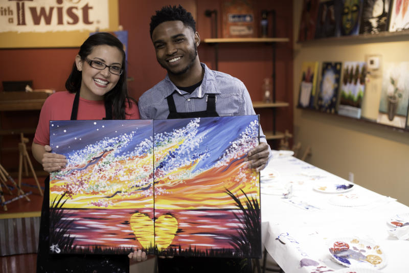 In this 2019 photo provided by Painting with a Twist, a couple reveals their date night art that when combined creates one piece of artwork they can display together, during a Painting with a Twist event in Mandeville, La. In recent years, the interactive painting industry has become a global sensation. Around the world, adults can spend their nights out learning to paint in a relaxed, BYOB setting. Thousands of franchises exist to help us all unleash our inner creative. (Painting with a Twist via AP)