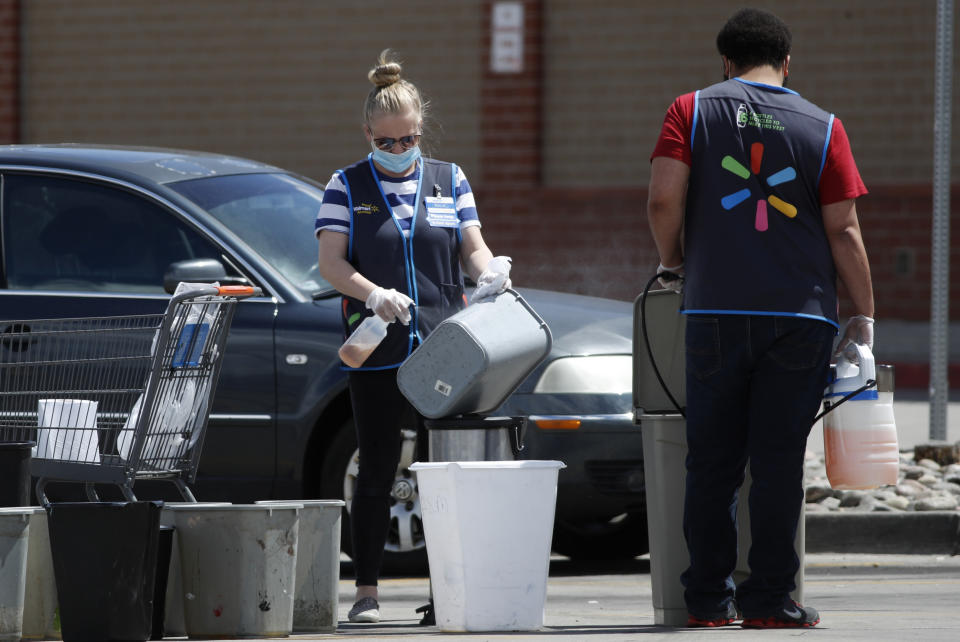 Workers sanitize items in the parking lot in front of a Walmart that has been closed following the deaths of three people connected to the store who were infected with the new coronavirus Friday, April 24, 2020, in Aurora, Colo. (AP Photo/David Zalubowski)