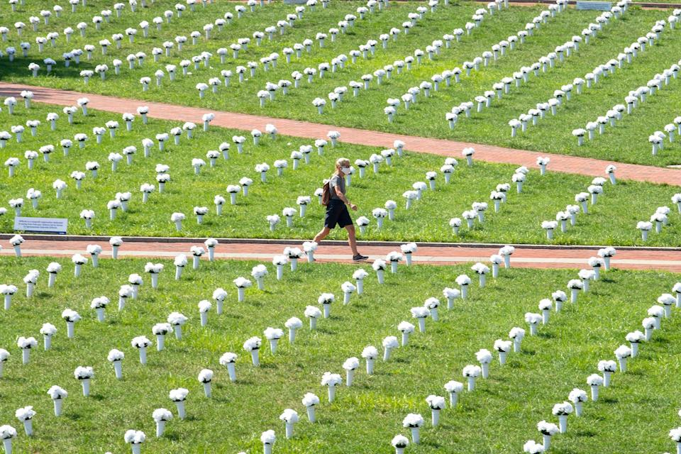 A pedestrian walks through a memorial adorned with white flowers and dedicated for victims of gun violence, Tuesday, Aug. 24, 2021, at Independence Mall in Philadelphia.