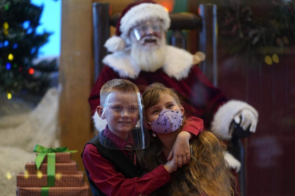 William Peargin, left, and Payton Peargin, right, both 8, pose for a socially distant photo with Santa Claus, who sits behind a sheet of plexiglass, at Bass Pro Shop in Rancho Cucamonga, Calif., on Dec. 4, 2020. In this socially distant holiday season, Santa Claus is still coming to towns (and shopping malls) across America but with a few 2020 rules in effect. (AP Photo/Ashley Landis)