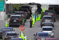 FILE - In this Nov. 18, 2020, file photo, vehicles line up as healthcare workers assist to check in citizens to be tested at the COVID-19 drive-thru testing center at Miami Beach Convention Center in Miami Beach, Fla. With coronavirus cases surging and families hoping to gather safely for Thanksgiving, long lines to get tested have reappeared across the U.S. (David Santiago/Miami Herald via AP, File)