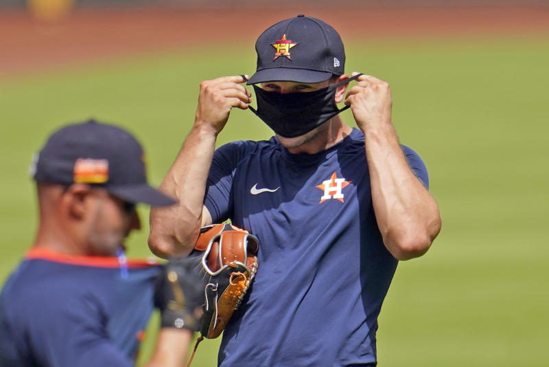 Houston Astros third baseman Alex Bregman, right, puts on a mask during a baseball practice Friday, July 3, 2020, at Minute Maid Park, in Houston. The Astros started workouts at the ballpark Friday as they and other Major League Baseball teams return amid the COVID-19 pandemic. (AP Photo/David J. Phillip)