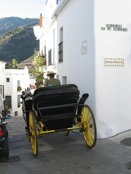 """This June 1, 2013 photo shows wedding guests leaving a church by horse carriage in Frigiliana, Spain. Frigiliana is one of Spain's """"pueblos blancos,"""" or white villages that sit high above the Mediterranean coast. (AP Photo/Giovanna Dell'Orto)"""
