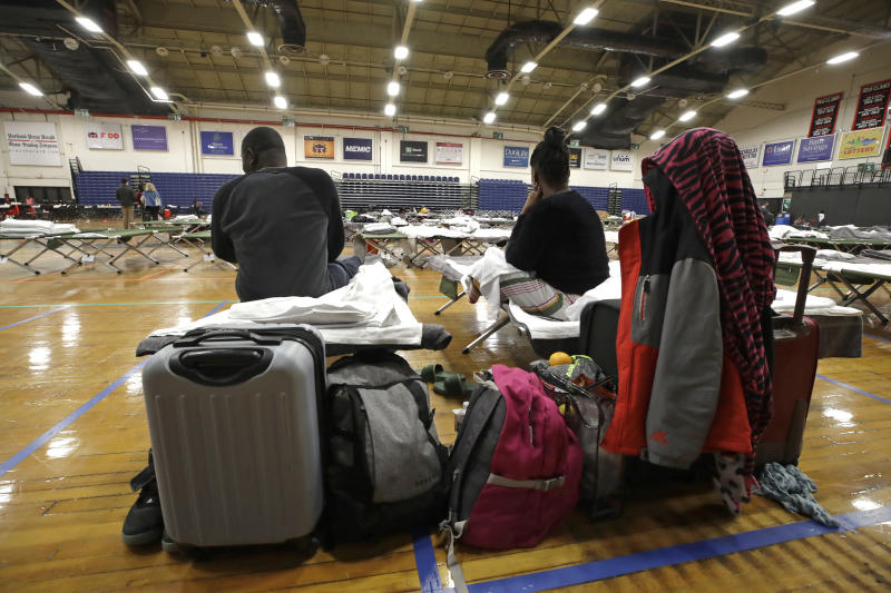 In this June 13, 2019 photo, a migrant couple sit with their belongings inside the Portland Exposition Building in Portland, Maine. Maine's largest city has repurposed the basketball arena as an emergency shelter in anticipation of hundreds of asylum seekers who are headed to the state from the U.S. southern border. Most are arriving from Congo and Angola. (AP Photo/Elise Amendola)