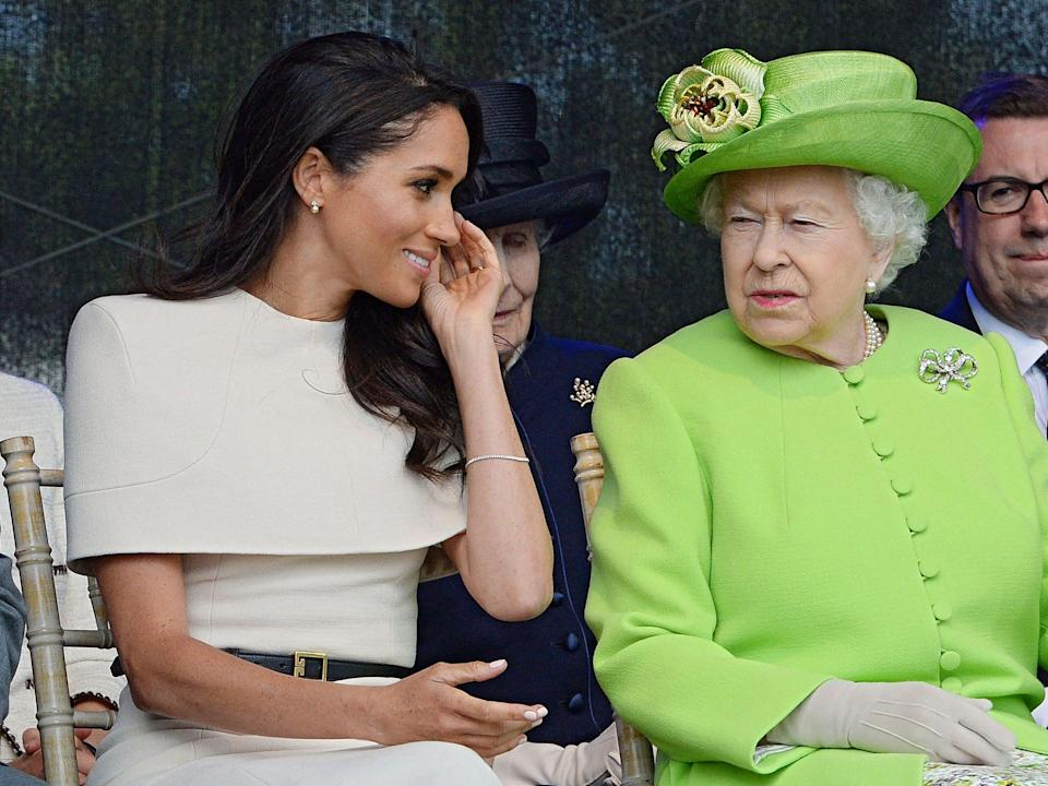 <p>In this file photo taken on June 14, 2018 Britain's Queen Elizabeth II and Meghan, Duchess of Sussex open the Mersey Gateway Bridge.</p> ((Photo by Jim CLARKE / POOL / AFP) (Photo by JIM CLARKE/POOL/AFP via Getty Images))