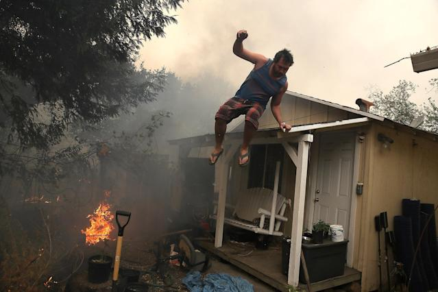 <p>A resident rushes to save his home as an out of control wildfire moves through the area on Oct. 9, 2017 in Glen Ellen, Calif. (Photo: Justin Sullivan/Getty Images) </p>