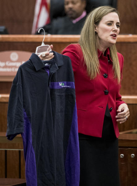 Prosecutor Samantha Knecht holds up a FedEx shirt, which was entered as evidence earlier in the trial, during closing arguments in Ronald Haskell's capital murder trial, Wednesday, Sept. 25, 2019, in Houston. Haskell is on trial for the 2014 shooting of six members of his ex-wife's family in suburban Houston.  (Brett Coomer/Houston Chronicle via AP)