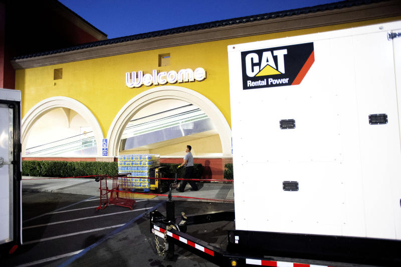 A portable generator powers a Lucky supermarket in Oakland, Calif., as Ruben Imperial moves water on Thursday, Oct. 10, 2019. The area remains without power after Pacific Gas and Electric cut service hoping to prevent wildfires during dry, windy conditions throughout Northern California. (AP Photo/Noah Berger)
