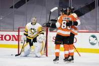 Philadelphia Flyers' Joel Farabee, center, celebrates his goal on Pittsburgh Penguins' goaltender Tristan Jarry, left, with Kevin Hayes, right, during the second period of an NHL hockey game, Wednesday, Jan. 13, 2021, in Philadelphia. (AP Photo/Chris Szagola)