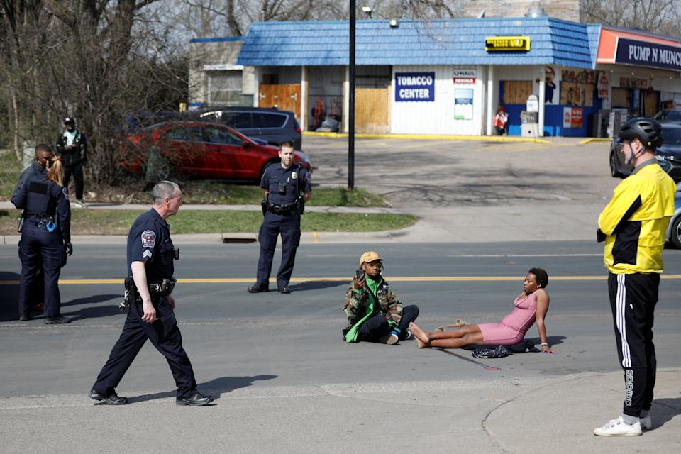 Phoenix Robles and Dorcas Monari sit in the street in Brooklyn Center, Minn. (Nick Pfosi/Reuters)