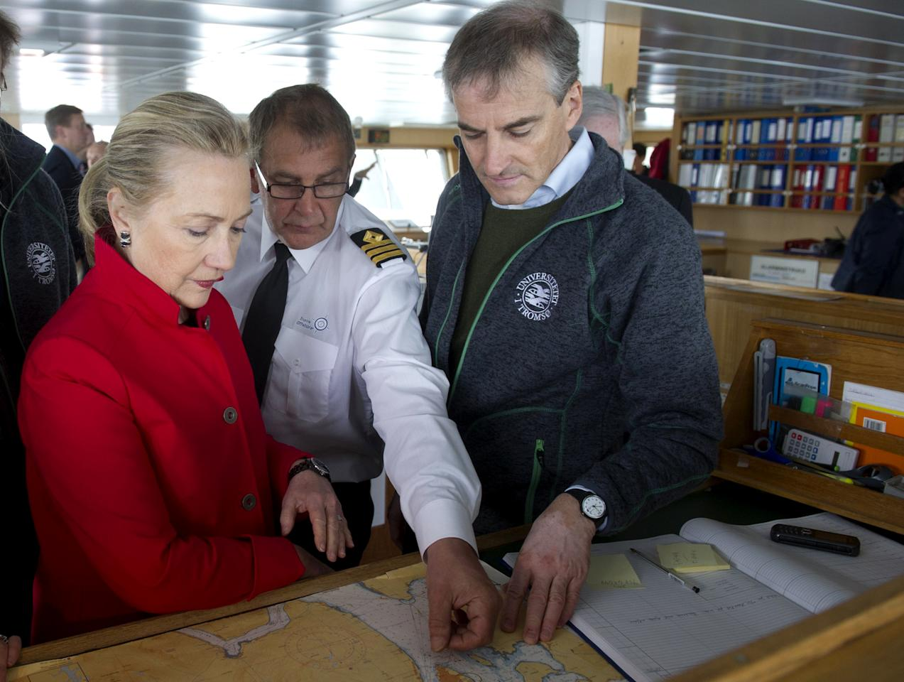 US Secretary of State Hillary Rodham Clinton, left, and Norway's Minister of Foreign Affairs Jonas Gahr Stoere, right, look at a map with First Officer Inge Einar Berg, center, aboard the Arctic Research Vessel Helmer Hanssen during a boat tour of the coastline, off the coast of Tromso, Norway, Saturday June 2, 2012. (AP Photo/Saul Loeb, Pool)