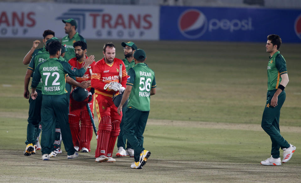 Zimbabwe's Sikandar Raza, and Brendan Taylor, in red, shakes hand with Pakistani players after the 3rd one-day international cricket match at the Pindi Cricket Stadium, in Rawalpindi, Pakistan, Tuesday, Nov. 3, 2020. (AP Photo/Anjum Naveed)