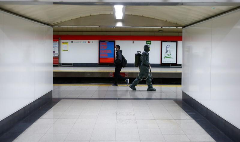 A Military Emergency Unit member disinfects Nuevos Ministerios metro station during a partial lockdown as part of a 15-day state of emergency to combat the spread of coronavirus disease (COVID-19) in Madrid