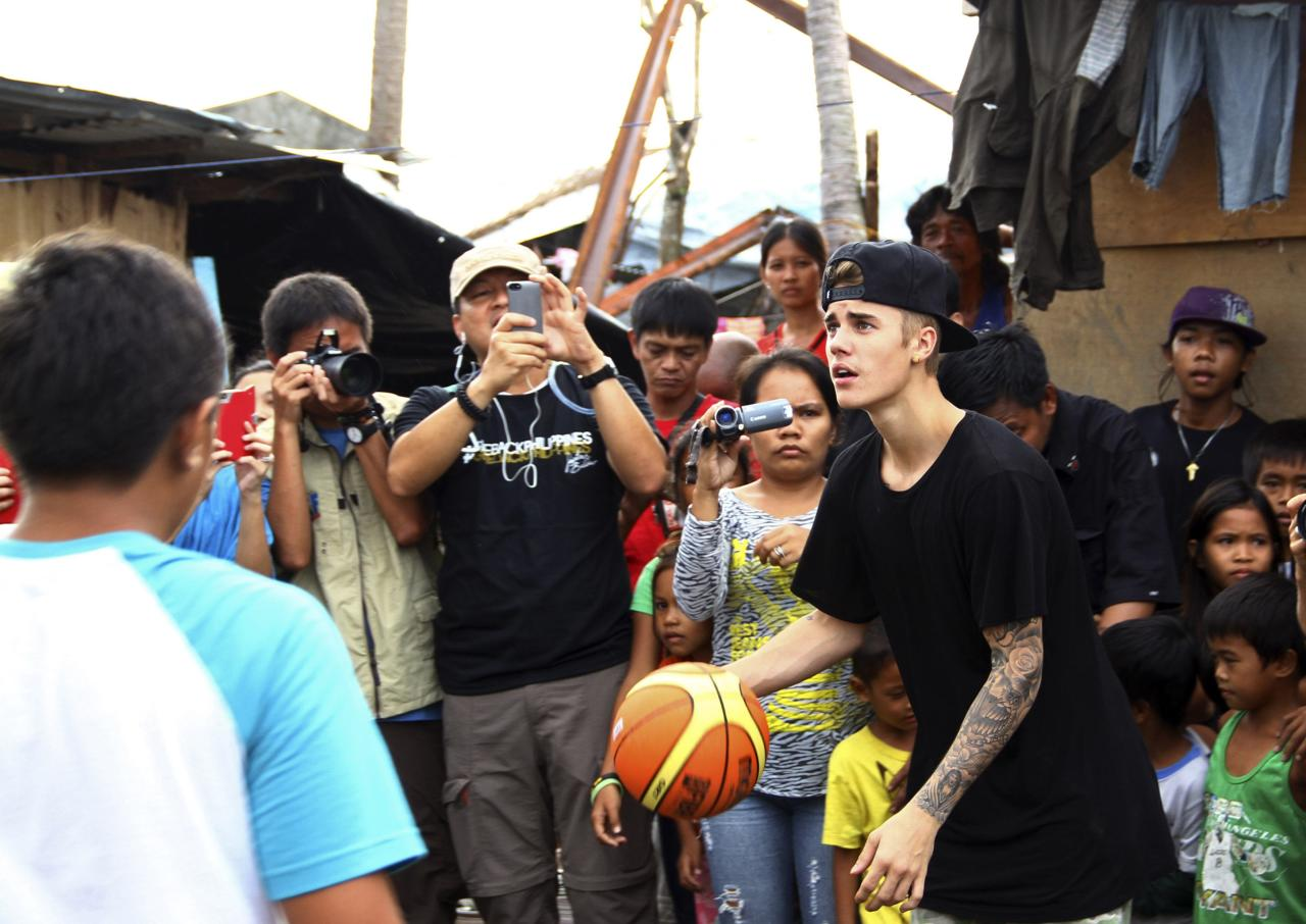 Pop singer Justin Bieber plays basketball during his visit to an evacuation centre at San Jose town, Tacloban city, central Philippines December 10, 2013. Bieber flew unannounced to Tacloban city on Tuesday to visit survivors a month after Typhoon Haiyan battered central Philippines, local media reported. REUTERS/Dennis Jay Santos (PHILIPPINES - Tags: ENTERTAINMENT POLITICS SPORT BASKETBALL)