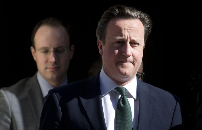 Britain's Prime Minister David Cameron, right, leaves 10 Downing Street for the House of Commons for the weekly session of Prime Minister's Question Time in the House of Commons, London, Wednesday, April 24, 2013. (AP Photo/Alastair Grant)