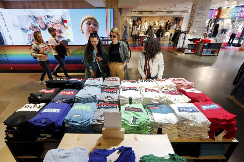 FILE - In this June 14, 2019 file photo a pair of shoppers, center, in the Levi's store in New York's Times Square, survey a T-shirt display. Manufacturers are facing stunted growth amid the damaging trade war between the U.S. and China, and that has some on Wall Street worried that it will crimp the consumer-fueled economy. Factory output has been slowing all year, and suffered its first contraction in three years during August. For now consumers are still doing much of the lifting for the U.S. economy. But a trade-war-damaged manufacturing sector could eventually dash consumer confidence and spending.  (AP Photo/Richard Drew, File)