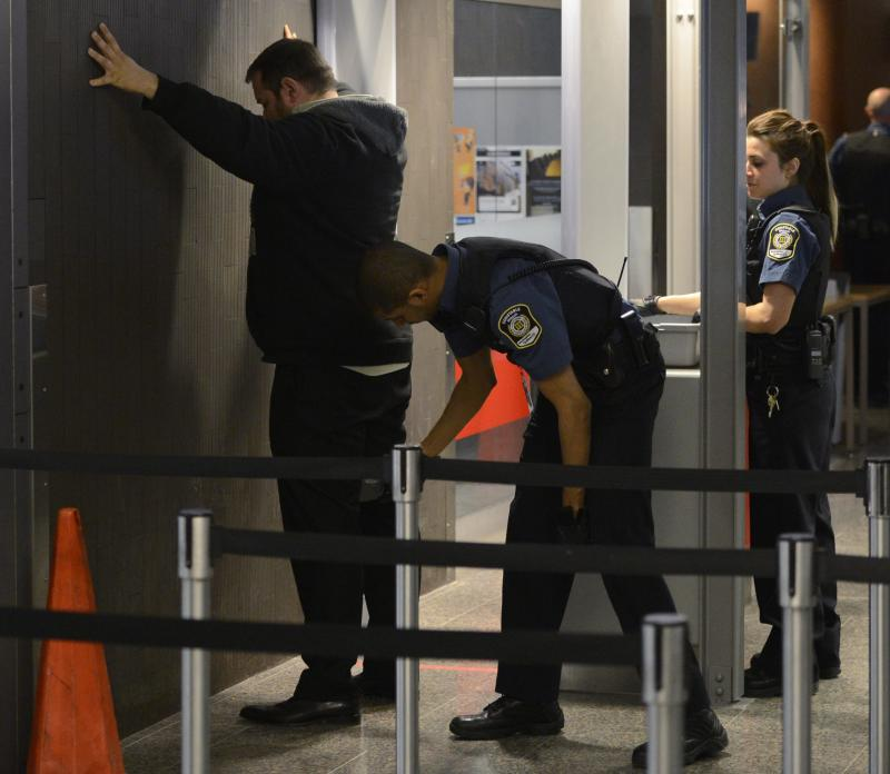 """Security officials check a man at a courthouse in Montreal on Tuesday, April 23, 2013. Reed Jaser, one of two men accused of plotting a terrorist attack against a Canadian passenger train with support from al-Qaida elements in Iran, made a brief court appearance Tuesday but did not enter a plea. Canadian investigators say Jaser, 35, and his suspected accomplice Chiheb Esseghaier, 30, received """"directions and guidance"""" from members of al-Qaida. The case prompted an immediate response from Iran, which denied any involvement and said groups such as al-Qaida do not share Iran's ideology.  (AP Photo/The Canadian Press, Ryan Remiorz)"""
