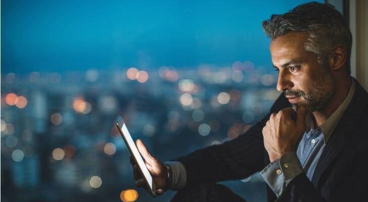 Businessman using his online trading app to invest