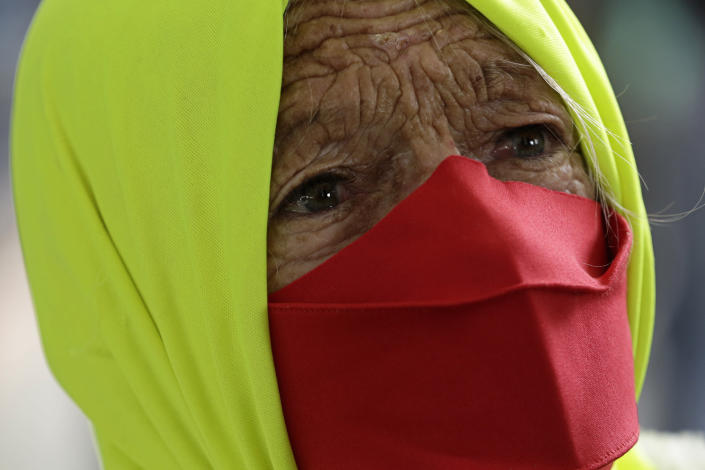 An elderly woman participates in a protest against Brazilian President Jair Bolsonaro's handling of the coronavirus in Brazilia, Brazil, Wednesday, Dec. 23, 2020. Protesters also called for the immediate start of COVID-19 vaccinations. (AP Photo/Eraldo Peres)
