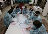 Members of a local electoral commission count ballots after polls closed during a parliamentary election in Almaty